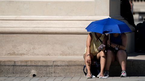 """TOPSHOT - People use an umbrella to shelter from the sun near the Louvre Pyramid (Pyramide du Louvre) during a heatwave in Paris on June 26, 2019. - Forecasters say Europeans will feel sizzling heat this week with temperatures soaring as high as 40 degrees Celsius (104 degrees Fahrenheit) in an """"unprecedented"""" June heatwave hitting much of Western Europe. (Photo by Kenzo TRIBOUILLARD / AFP)        (Photo credit should read KENZO TRIBOUILLARD/AFP/Getty Images)"""