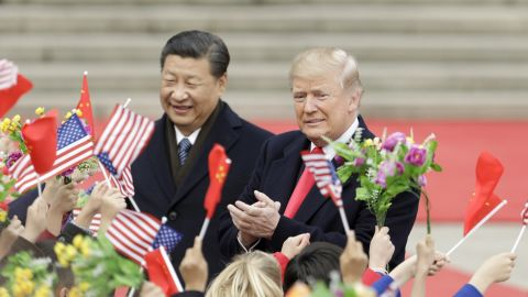 US President Donald Trump, right, and Xi Jinping, China's president, greet attendees waving American and Chinese national flags during a welcome ceremony outside the Great Hall of the People in Beijing, China, on Thursday, Nov. 9, 2017. Photographer: Qilai Shen/Bloomberg via Getty Images