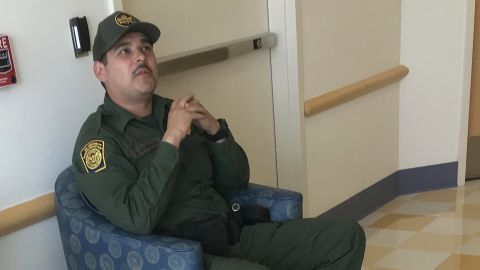A border agent sits outside the hospital room of an 16-year-old migrant girl.