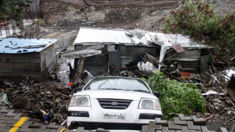 A damaged vehicle is seen at the site of the wall collapse in Pune.