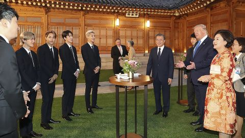 President Donald Trump talks with South Korean K-pop band EXO as South Korean President Moon Jae-in looks on at the presidential Blue House in Seoul on Saturday, June 29.