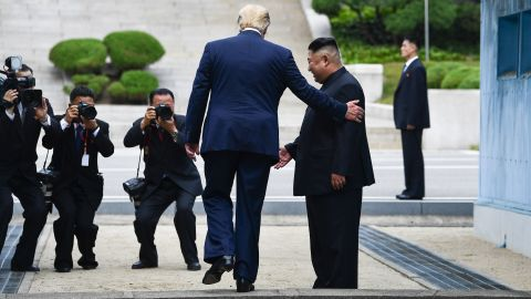 US President Donald Trump steps into the northern side of the Military Demarcation Line that divides North and South Korea, as North Korea's leader Kim Jong Un looks on, in the Joint Security Area (JSA) of Panmunjom in the Demilitarized zone (DMZ) on June 30, 2019.