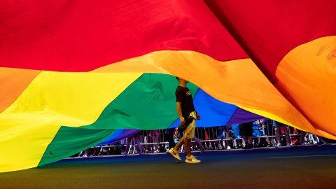 A participant walks under a large rainbow flag.