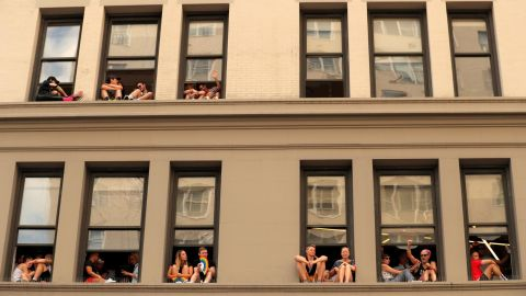 People watch from windows on 6th Avenue along the parade route.