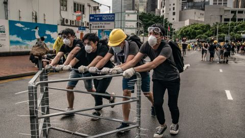 Anti-extradition protesters move barricades on a street outside the Legislative Council Complex ahead of the annual flag raising ceremony of 22nd anniversary of the city's handover from Britain to China on July 1, 2019 in Hong Kong, China. Pro-democracy demonstrators in Hong Kong have organized rallies over the past weeks, calling for the withdrawal of a controversial extradition bill, the resignation of the territory's chief executive Carrie Lam, an investigation into police brutality, and drop riot charges against peaceful protesters. (Photo by Anthony Kwan/Getty Images)