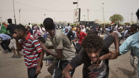 Protesters run from a police van that drove through a crowd on June 30 in Khartoum. The protesters faced off with armed forces on a main road leading to the airport.