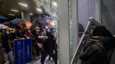 This picture taken on July 1, 2019 shows protesters smashing glass doors and windows of the legislature in Hong Kong.