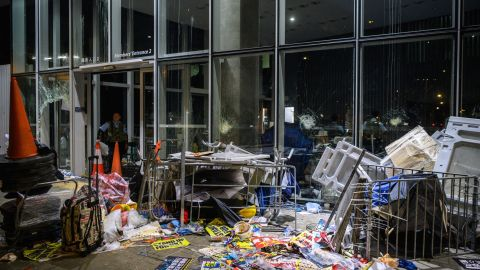 A policeman looks at the damage and debris after protesters stormed the legislature hours before in Hong Kong early on July 2, 2019.
