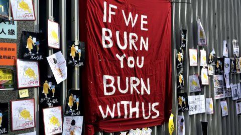 "A flag reading ""If we burn, you burn with us,"" erected outside Hong Kong's legislature on July 1, 2019."