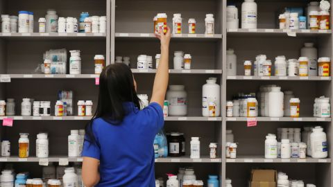 """MIDVALE, UT - SEPTEMBER 10: A pharmacy technician grabs a bottle of drugs off a shelve at the central pharmacy of Intermountain Heathcare on September 10, 2018 in Midvale, Utah. IHC along with other hospitals and philanthropies are launching a nonprofit generic drug company called """"Civica Rx"""" to help reduce cost and shortages of generic drugs.  (Photo by George Frey/Getty Images)"""