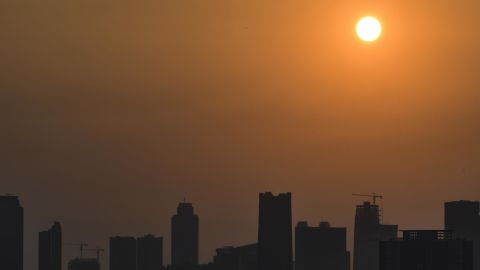 The morning sun rises past buildings and haze over the Jakarta city skyline on August 17, 2018.