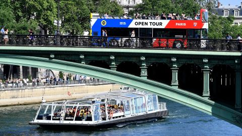 Tourists enjoy a ride on a tourist river boat (Bateaux-Mouche)and tourism bus on the Seine river on a sunny day in Paris on May 6, 2018. (Photo by GERARD JULIEN / AFP)        (Photo credit should read GERARD JULIEN/AFP/Getty Images)