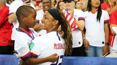 US forward Jessica McDonald holds her son, Jeremiah, after the France win.