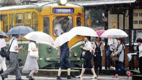 People walk in the rain in Kagoshima, southwest Japan, on July 2, 2019.