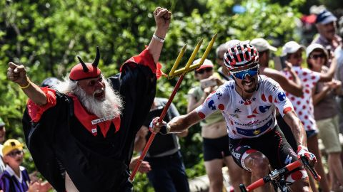 """France's Julian Alaphilippe, wearing the best climber's polka dot jersey, seizes the fork of legendary Tour de France fan Didi Senft, nicknamed """"The Devil,"""" during the 17th stage of last year's race. """"The Devil"""" is sure ot make his customary appearances this year."""