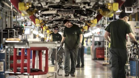 """Employees work underneath Jaguar automobiles on the final assembly line at Tata Motors Ltd.'s Jaguar assembly plant in Castle Bromwich, U.K., on Thursday, March 16, 2017. Jaguar Land Rover Chief Executive Officer Ralf Speth backed Nissan Motor Co.'s calls for extra funding for car-parts makers in the wake of last years Brexit vote, while cautioning that there must be """"fair play"""" for all U.K. automakers. Photographer: Simon Dawson/Bloomberg via Getty Images"""