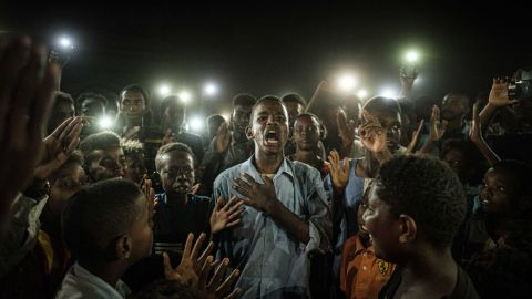 People chant slogans as a young man recites a poem, illuminated by mobile phones on June 19.
