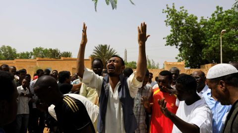 Relatives of three Sudanese men who were found dead with bullet wounds mourn near their bodies in the city of Omdurman on July 1.