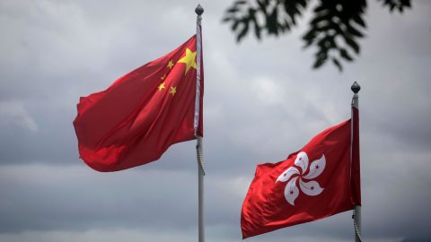 The China national flag (L) is seen beside the Hong Kong flag in Hong Kong on July 2, 2019, a day after protesters broke into the government headquarters.