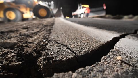 Highway workers repair a hole in a road that opened as a result of the July 5 earthquake in Ridgecrest, California.
