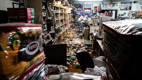 An employee stands behind the counter amid fallen bottles at a gas station and liquor store in Ridgecrest, California, on July 6, 2019.