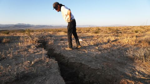 RIDGECREST, CALIFORNIA - JULY 04:  A local resident inspects a crack in the earth after a 6.4 magnitude earthquake struck the area on July 4, 2019 near Ridgecrest, California. The earthquake was the largest to strike Southern California in 20 years with the epicenter located in a remote area of the Mojave Desert. The temblor was felt by residents across much of Southern California. (Photo by Mario Tama/Getty Images)