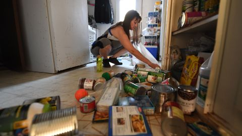 Tammy Sears cleans up her kitchen on July 6, 2019, after a magnitude 7.1 earthquake dumped food items on the floor  of her mobile home in Ridgecrest, California.