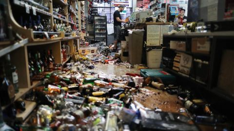 An employee works at the cash register on July 6 at Eastridge Market, near broken bottles scattered on the floor, following a 7.1 magnitude earthquake which struck in the area July 5.