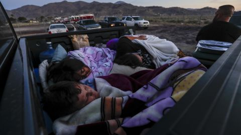 The Horta family, forced from their home as a result of the earthquake, sleeps in the bed of their pickup truck at a fire station parking lot on July 6 in Trona, California.