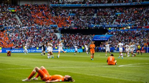Dutch players fall to the ground as the Americans celebrate their victory.