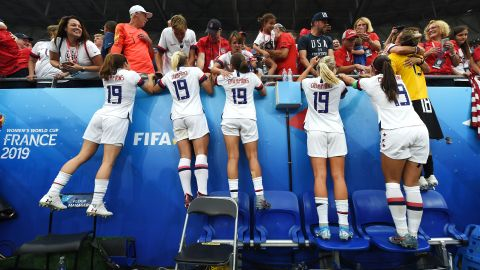 """US players, wearing new """"Champions 19"""" jerseys, celebrate with family and friends in the crowd."""