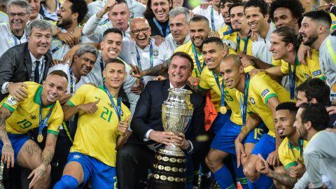 Brazilian President Jair Bolsonaro holds the Copa America trophy as members of the national team celebrate.