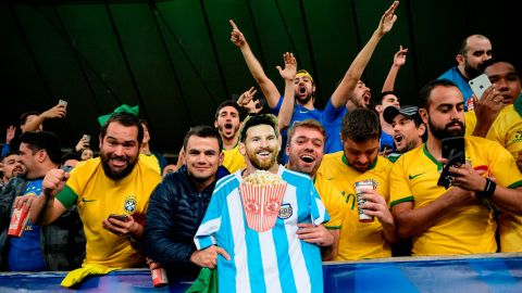 Fans of Brazil hold an image of Argentine footballer Lionel Messi eating popcorn as they celebrate.