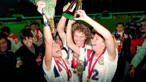 Michelle Akers-Stahl (C) who scored two goals for the US to win the first FIFA World Championship for Women's Football on November 30, 1991, holds the trophy together with teammates Julie Foudy (L) and Carin Jennings (R). The US won the championship by beating Norway 2-1. The FIFA Women's World Cup is recognized as the most important International competition in women's football and is played amongst women's national football teams of the member states of FIFA. Contested every four years, the first Women's World Cup tournament, named the Women's World Championship, was held in 1991, sixty-one years after the men's first FIFA World Cup tournament in 1930AFP PHOTO TOMMY CHENG (Photo by TOMMY CHENG / AFP)        (Photo credit should read TOMMY CHENG/AFP/Getty Images)