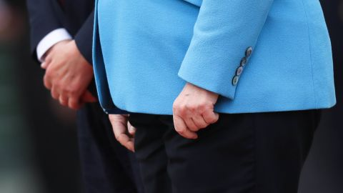 The hands of Merkel and Finnish Prime Minister Antti Rinne are seen as they listen to national anthems in Berlin in July 2019. Merkel's body <a href=