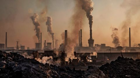 """INNER MONGOLIA, CHINA - NOVEMBER 04: Smoke billows from a large steel plant as a Chinese labourer works at an unauthorized steel factory, foreground, on November 4, 2016 in Inner Mongolia, China. To meet China's targets to slash emissions of carbon dioxide, authorities are pushing to shut down privately owned steel, coal, and other high-polluting factories scattered across rural areas. In many cases, factory owners say they pay informal 'fines' to local inspectors and then re-open. The enforcement comes as the future of U.S. support for the 2015 Paris Agreement is in question, leaving China poised as an unlikely leader in the international effort against climate change. U.S. president-elect Donald Trump has sent mixed signals about whether he will withdraw the U.S. from commitments to curb greenhouse gases that, according to scientists, are causing the earth's temperature to rise. Trump once declared that the concept of global warming was """"created"""" by China in order to hurt U.S. manufacturing. China's leadership has stated that any change in U.S. climate policy will not affect its commitment to implement the climate action plan. While the world's biggest polluter, China is also a global leader in establishing renewable energy sources such as wind and solar power. (Photo by Kevin Frayer/Getty Images)"""