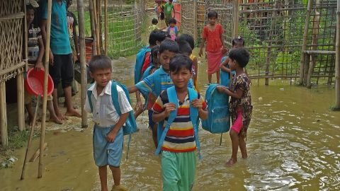 Rohingya children walk in floodwater to their learning center at a refugee camp in Bangladesh.