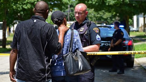 Police investigators in Cleveland talk with two bystanders.