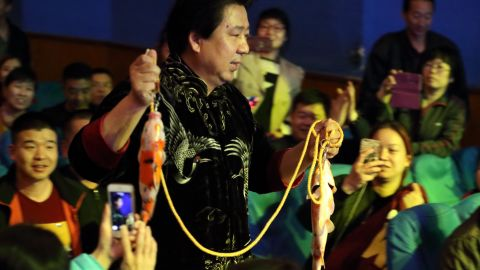 Audience members take pictures of Tian performing his carp illusion.
