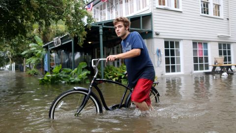 Logan Courvlle pushes his bike through a flooded street after Hurricane Barry in Mandeville, Louisiana, on July 13.
