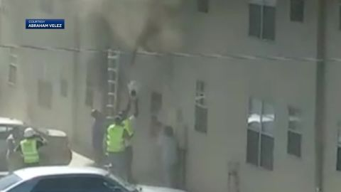 This still image was taken from video showing Mason Fierro catching a baby from a second-story apartment during a fire in northeast Albuquerque.