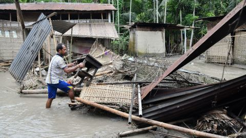 An Indian woman searches her belongings near the debris of her house following floodwaters in Kasuarbori village, in the Indias northeastern state of Assam, on July 13, 2019. - At least 17 people have been killed across Nepal after torrential monsoon rains induced floods and landslides, officials said on July 12.