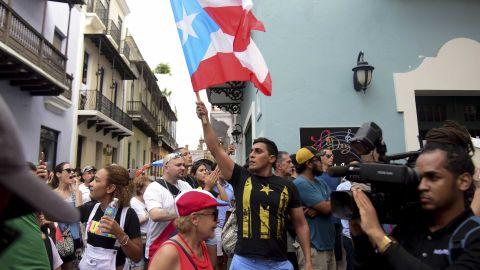 """Crowds flooded the streets of Old San Juan carrying Puerto Rican flags and signs that read """"Ricky Resign"""" in Spanish."""