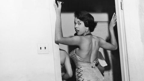 Blues singer Della Reese is eased into her snug-fitting gown by her dresser during a 1957 engagement at Robert's Show Lounge in Chicago, Illinois.