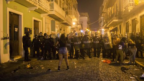 A demonstrator reacts in front of the police during clashes in San Juan, Puerto Rico, Wednesday, July 17, 2019. Thousands of people marched to the governor's residence in San Juan on Wednesday chanting demands for Gov. Ricardo Rossello to resign after the leak of online chats that show him making misogynistic slurs and mocking his constituents. (AP Photo/Dennis M. Rivera Pichardo)