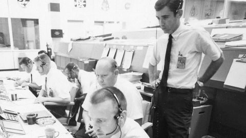 The Apollo 11 flight dynamics team included Jerry Bostick, seen here standing behind Philip Shaffer and David Reed.