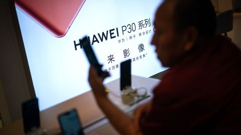 A customer looks at a smartphone at a Huawei retail store in Beijing on May 23, 2019. - Chinese telecom giant Huawei says it could roll out its own operating system for smartphones and laptops in China by the autumn after the United States blacklisted the company, a report said on May 23. (Photo by FRED DUFOUR / AFP)        (Photo credit should read FRED DUFOUR/AFP/Getty Images)