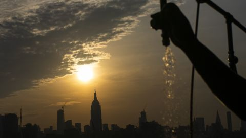 The sun rises over New York City and the Empire State Building while a man sprays water at Pier A.
