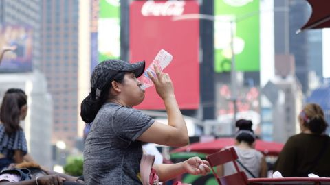 A woman drinks water in Times Square as temperatures reach the mid-to-upper 90s.