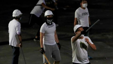 Men in white T-shirts with poles are seen in Yuen Long after attacking anti-extradition bill demonstrators at a train station, in Hong Kong.